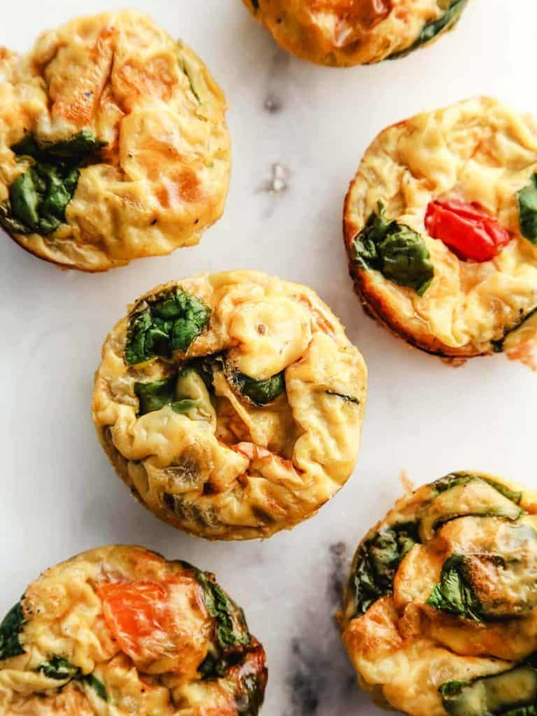 A white marble table with 6 tomato and spinach egg muffins.