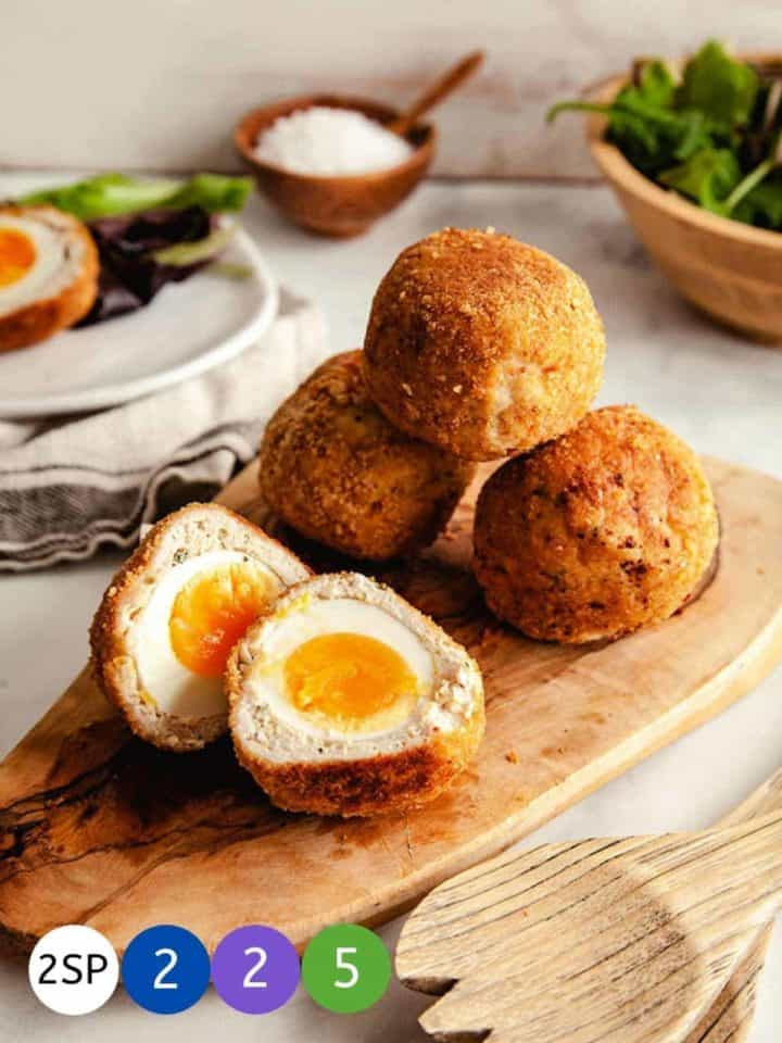 4 Scotch eggs on a wooden board - one cut in half to show the yellow yolk.