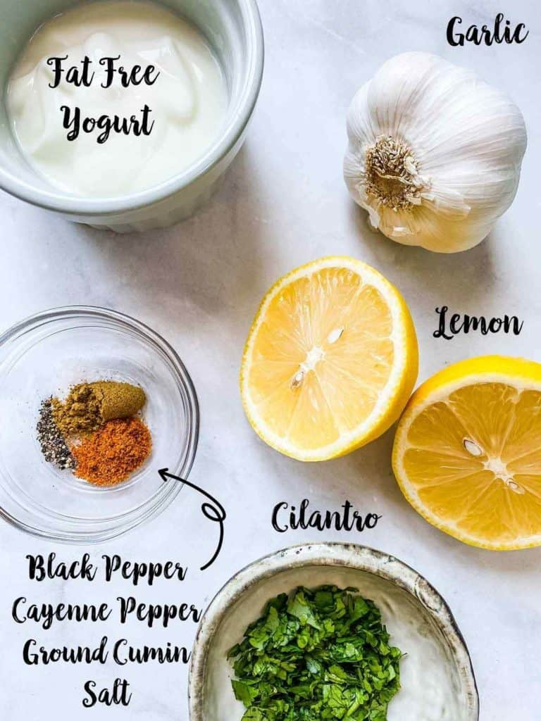 A pot of yogurt, a garlic bulb, a lemon, some spices and a bowl of chopped cilantro on a white table all with text labels.