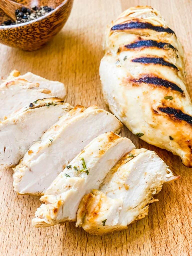 2 chicken breasts with grill marks, one sliced one whole on a wooden table.