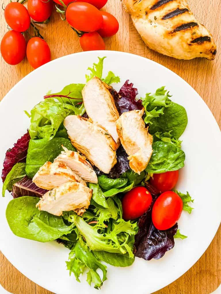 A white bowl full of lettuce and tomatoes with sliced chicken on top.