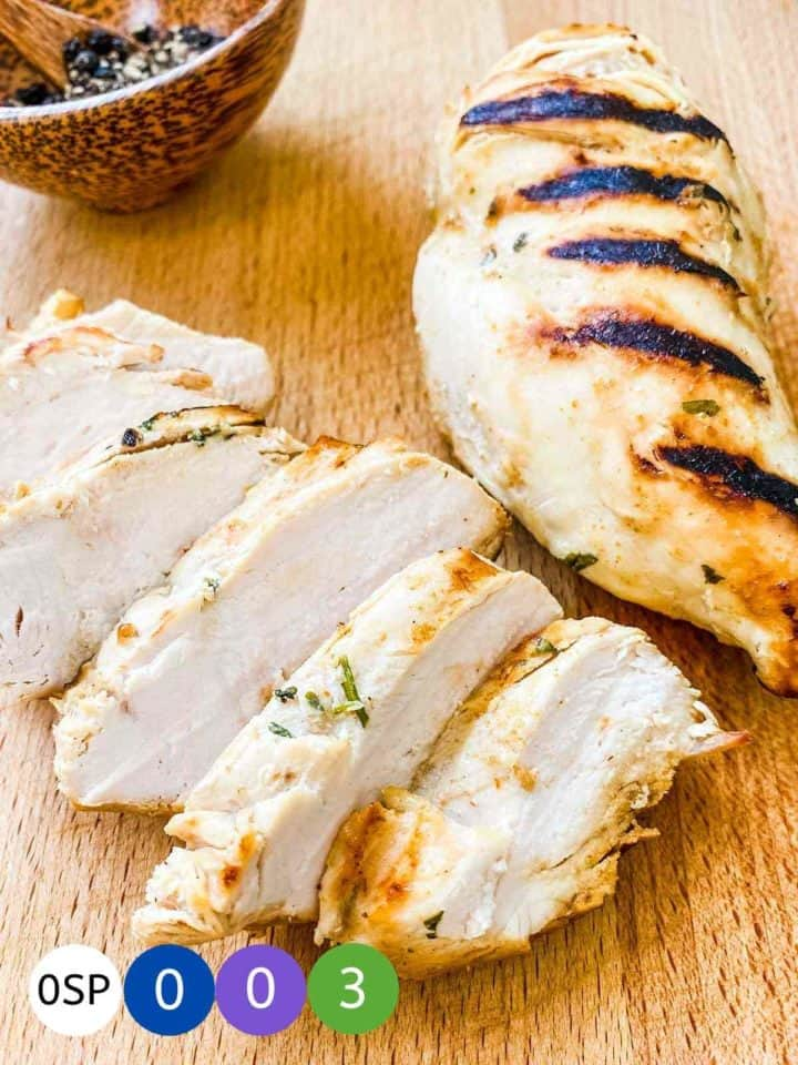 2 chicken breasts with grill marks on a wooden board.