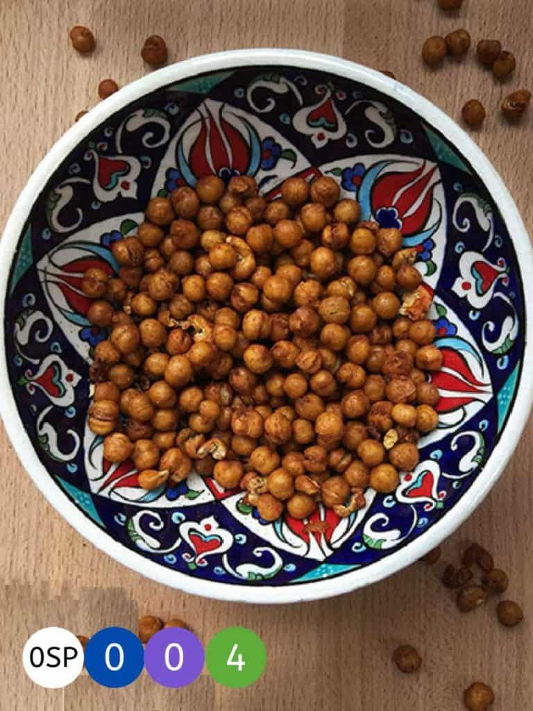 A red and blue painted bowl on a wooden table with roasted chickepeas.