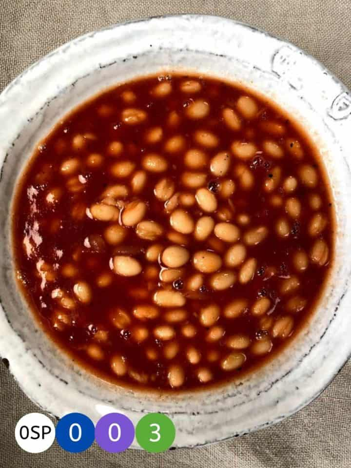 A white ceramic bowl full of bbq baked beans.