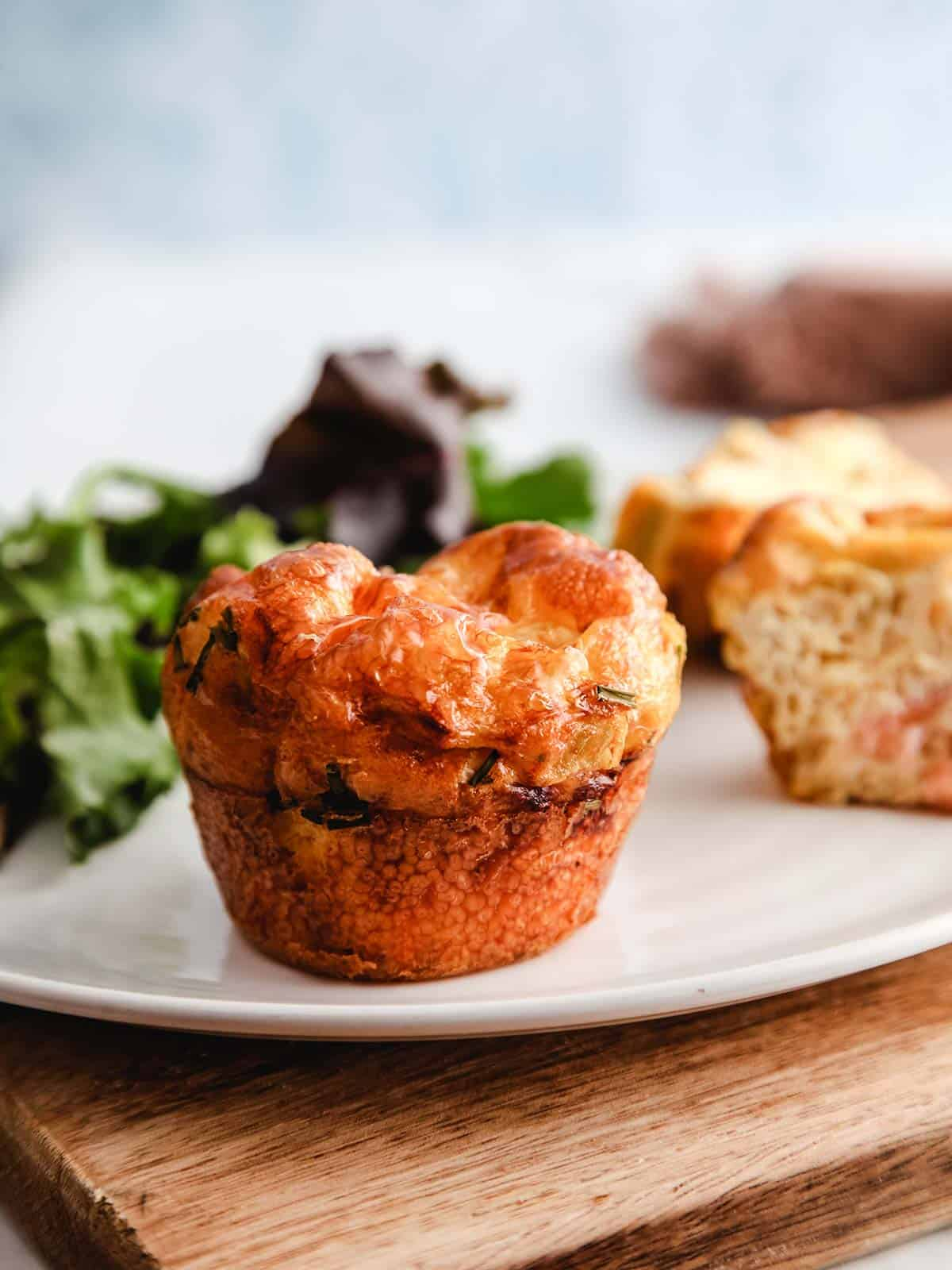 Breakfast muffins on a white plate on a wooden board.