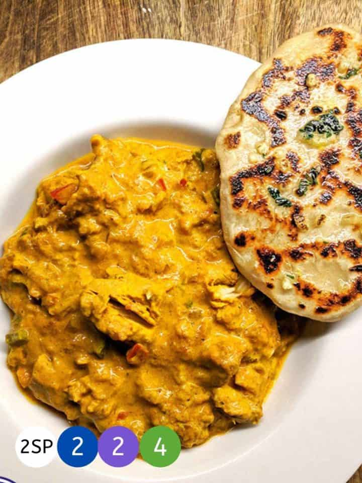 A white ceramic dish full of chicken tikka masala and a naan bread.