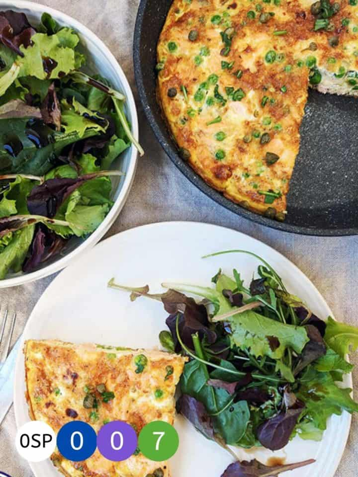 A skillet and plate of salmon & pea frittata with a side salad.