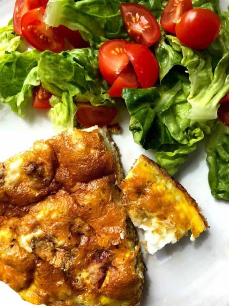 A white plate with a slice of frittata and a green salad.