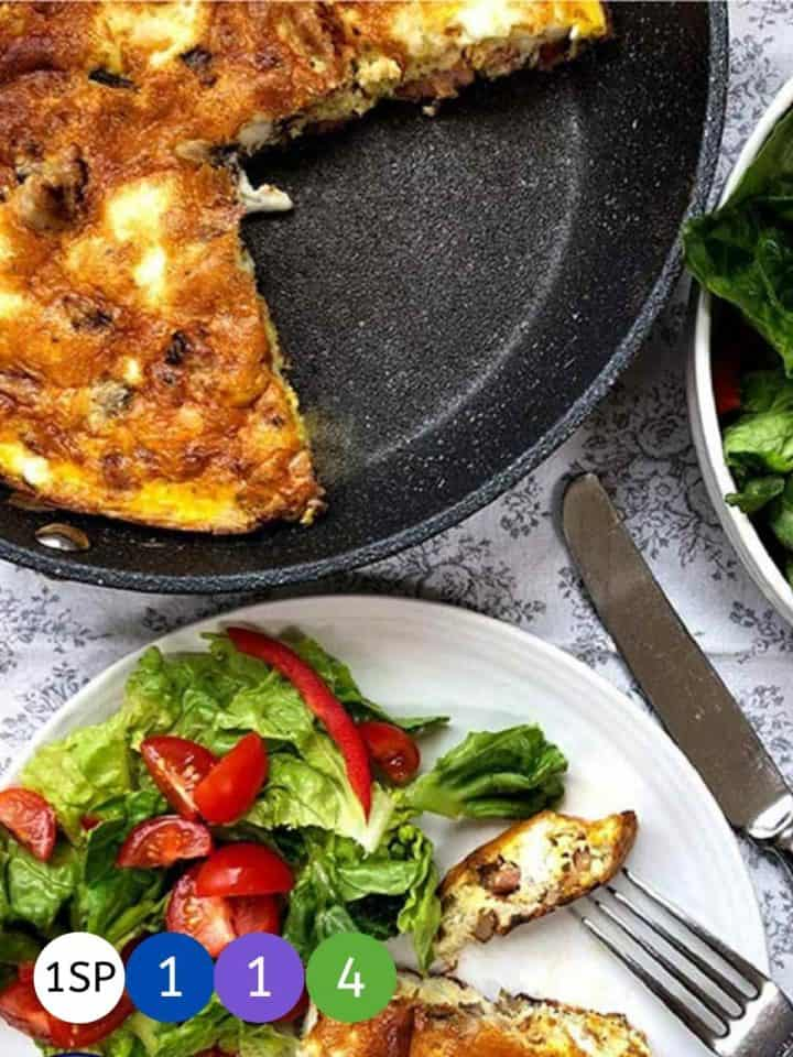 A skillet of frittata with a slice on a plate with a green salad.