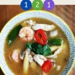A dish of soup on a wooden table with text overlay stating 'Weight Watchers Tom Yum Soup' and the SmartPoint values