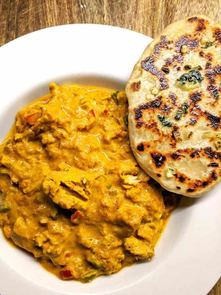 A white bowl full of chicken tikka masala and a naan bread.