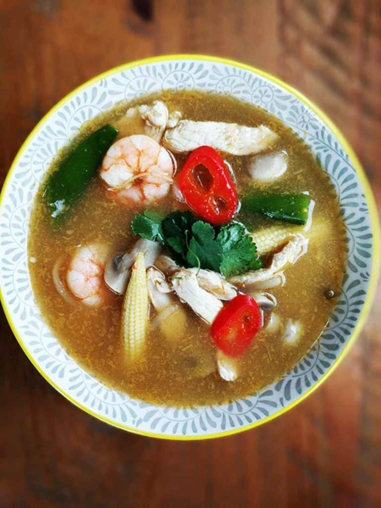 A bowl of tom yum soup on a wooden table.