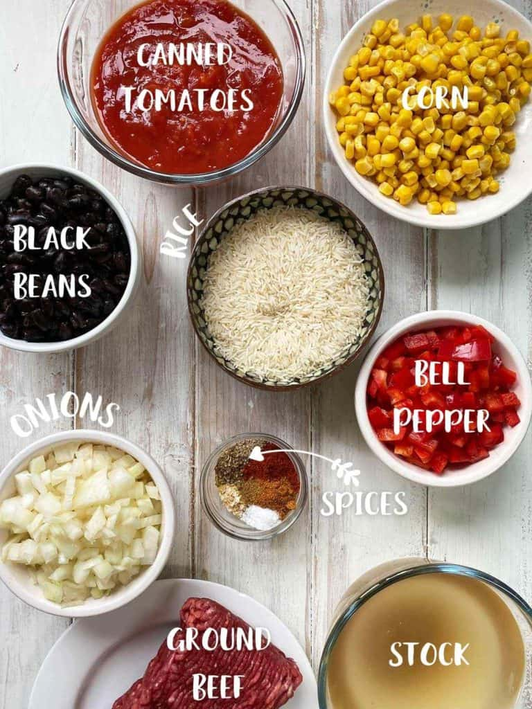 All of the ingredients to make burrito bowl in small bowls with text description.
