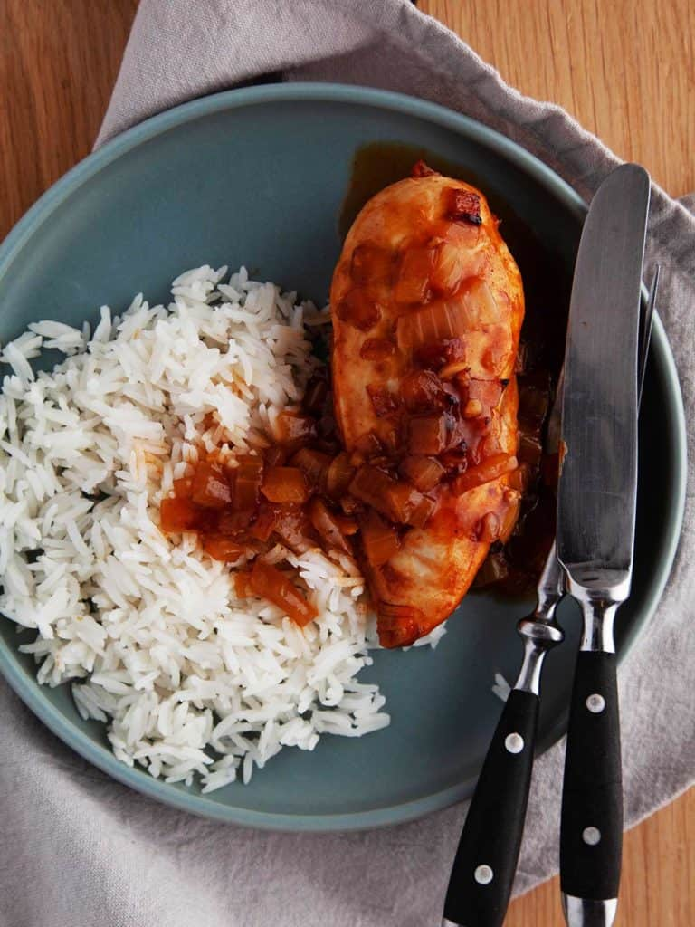 A blue plate on a linen napkin with white rice and chicken in ginger beer sauce.