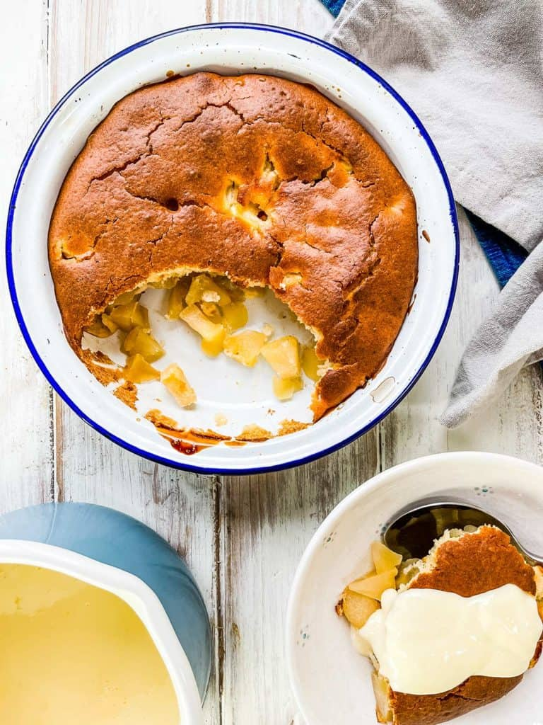 A dish of apple sponge pudding on a white table with a dish of dessert with custard on top to the side.