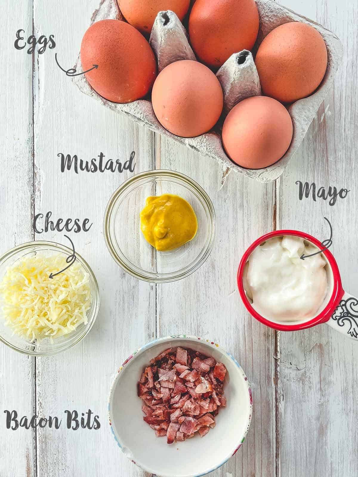 Ingredients that are used for deviled eggs on a white wooden table with label text overlay.