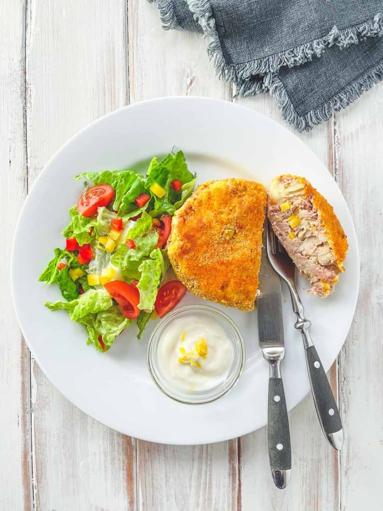 A white plate with a tuna & Sweetcorn fishcake and some salad on a white wooden table.