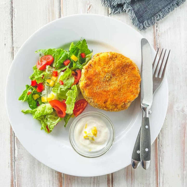 A white plate with a fishcake and some salad on a white wooden table.