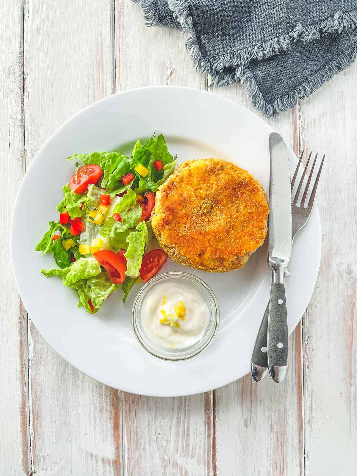 A white plate with a tuna & Sweetcorn fish cake and some salad on a white wooden table.