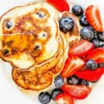 A white plate with pancakes and berries and topped with syrup and graphics showing the Weight Watchers smartpoint values.