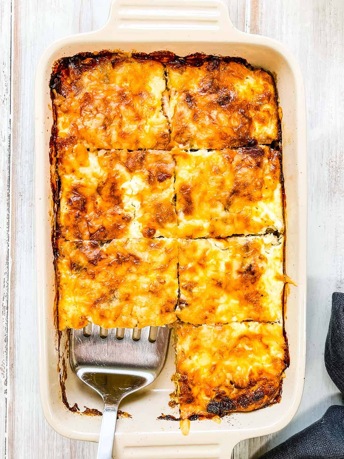 The baked casserole cut into 8 slices with one piece missing.