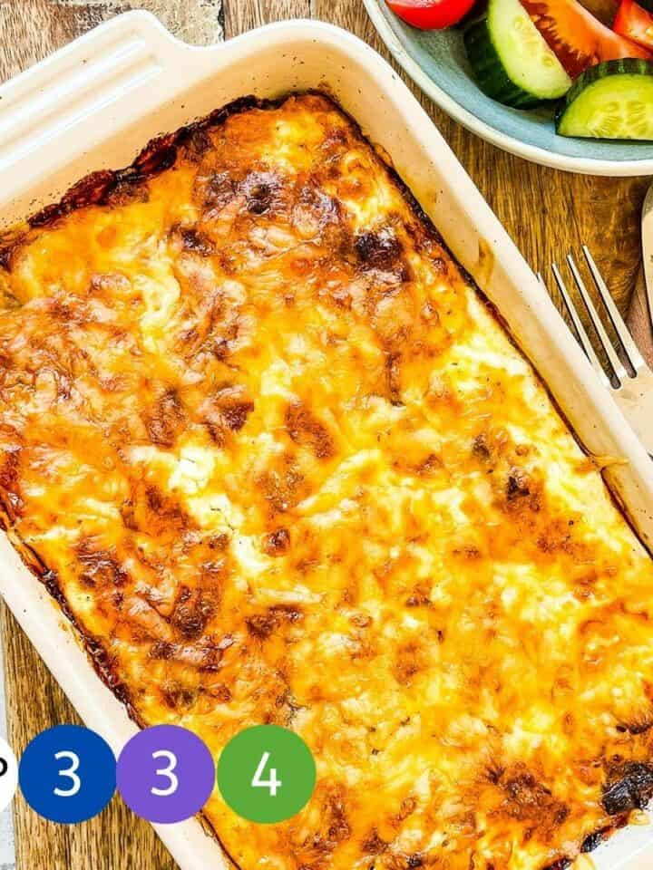 A baked casserole on a wooden board with graphics of the WW Smartpoint values.