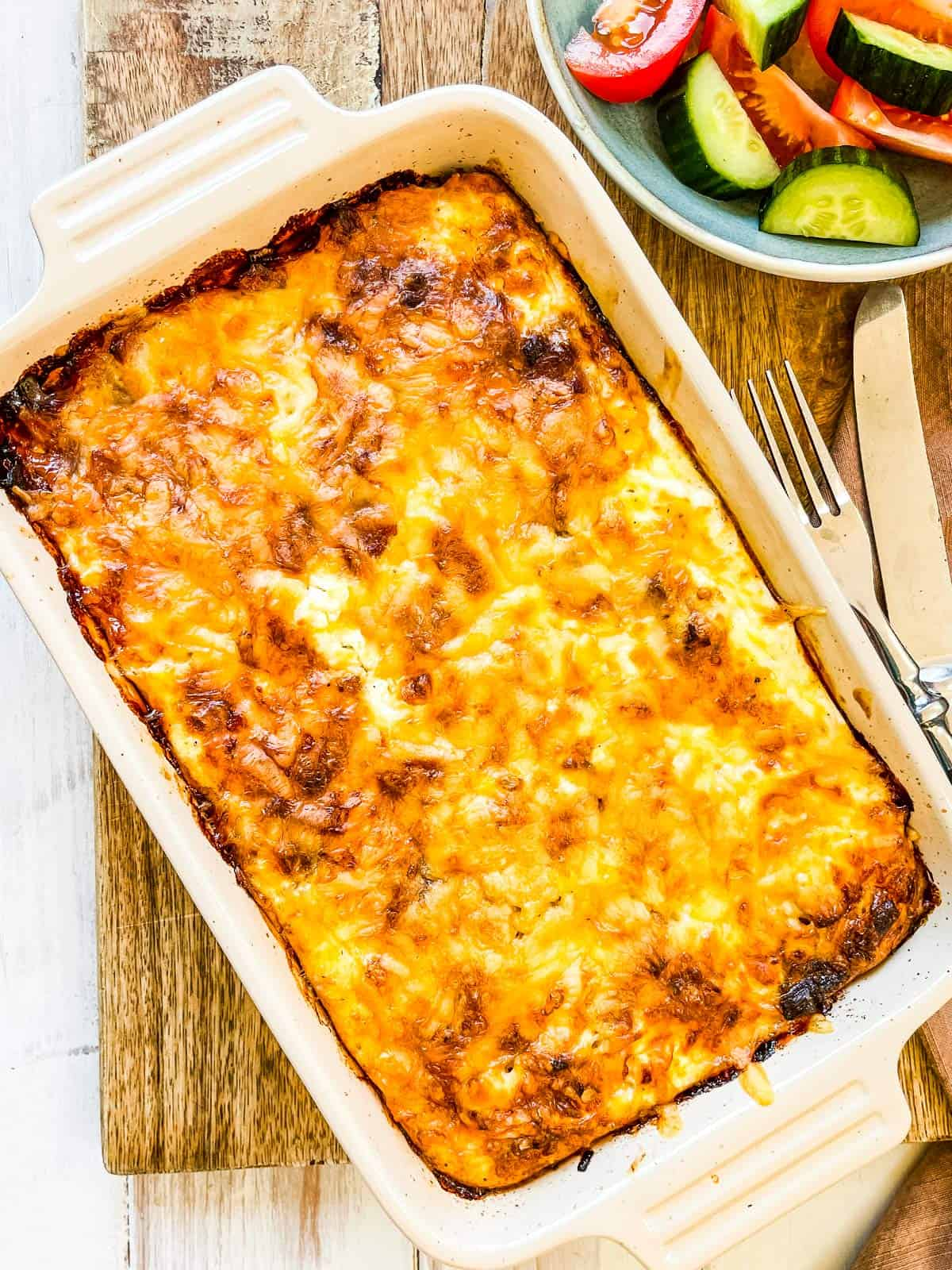 A baked casserole on a wooden board with a side dish on the side.