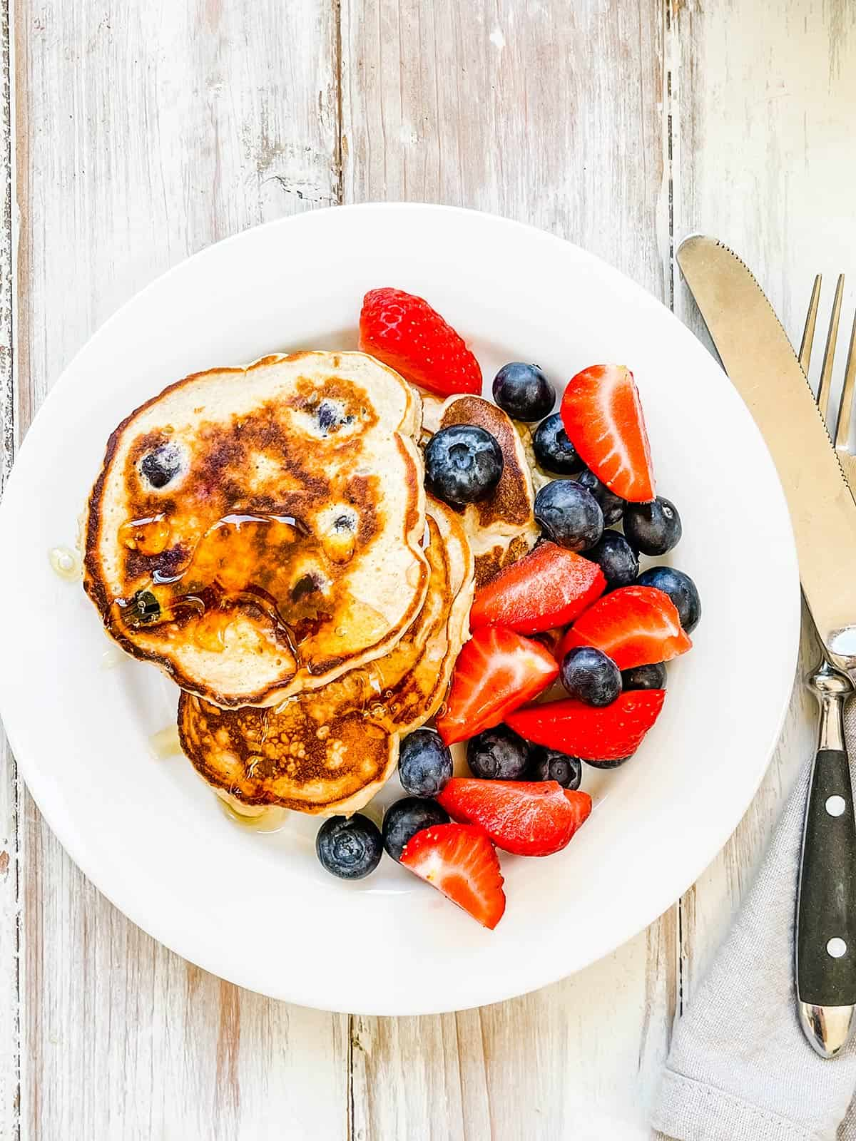 A plate of pancakes with mixed berries on a white table.