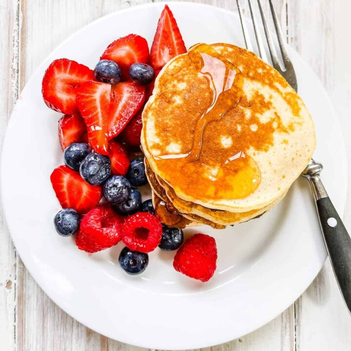 A white plate with a stack of pancakes and syrup and mixed berries.