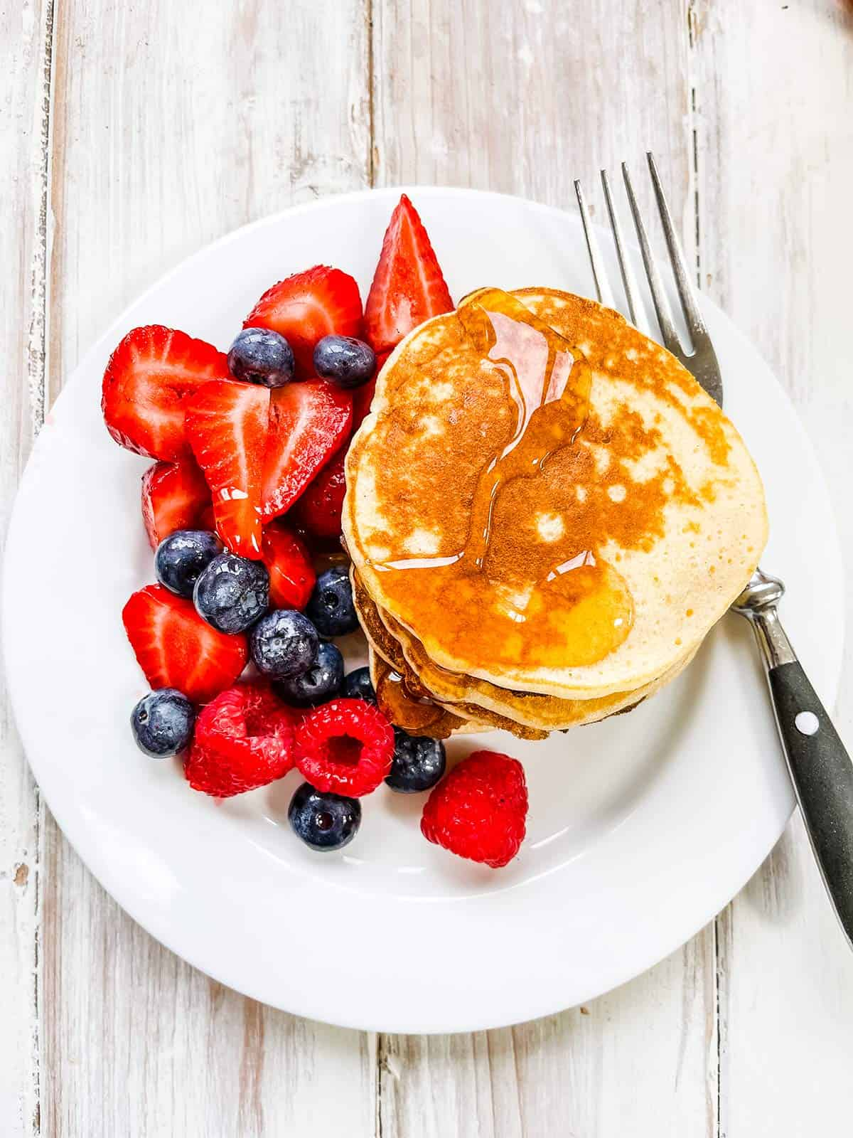 A white plate on a white table with mixed berries and a stack of pancakes.
