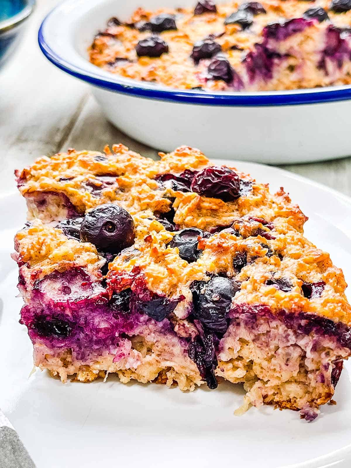 A white plate on a white table with blueberry baked oatmeal.