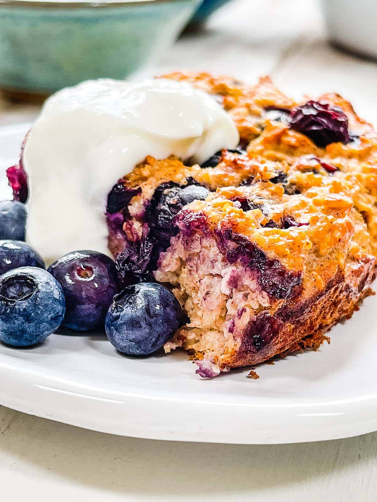 A white plate with baked oatmeal and blueberries and yogurt.