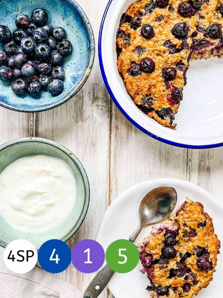 A dish of baked oatmeal on a white table with dishes of blueberries and yogurt.
