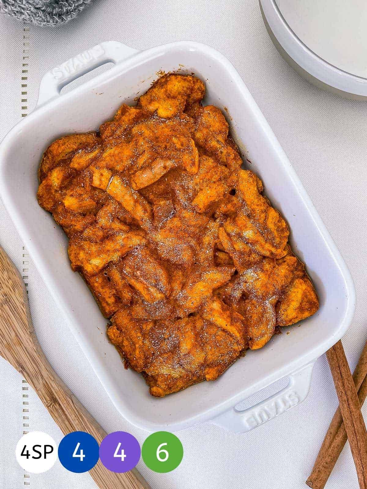 A dish of pumpkin french toast casserole on a white table with cinnamon sticks.