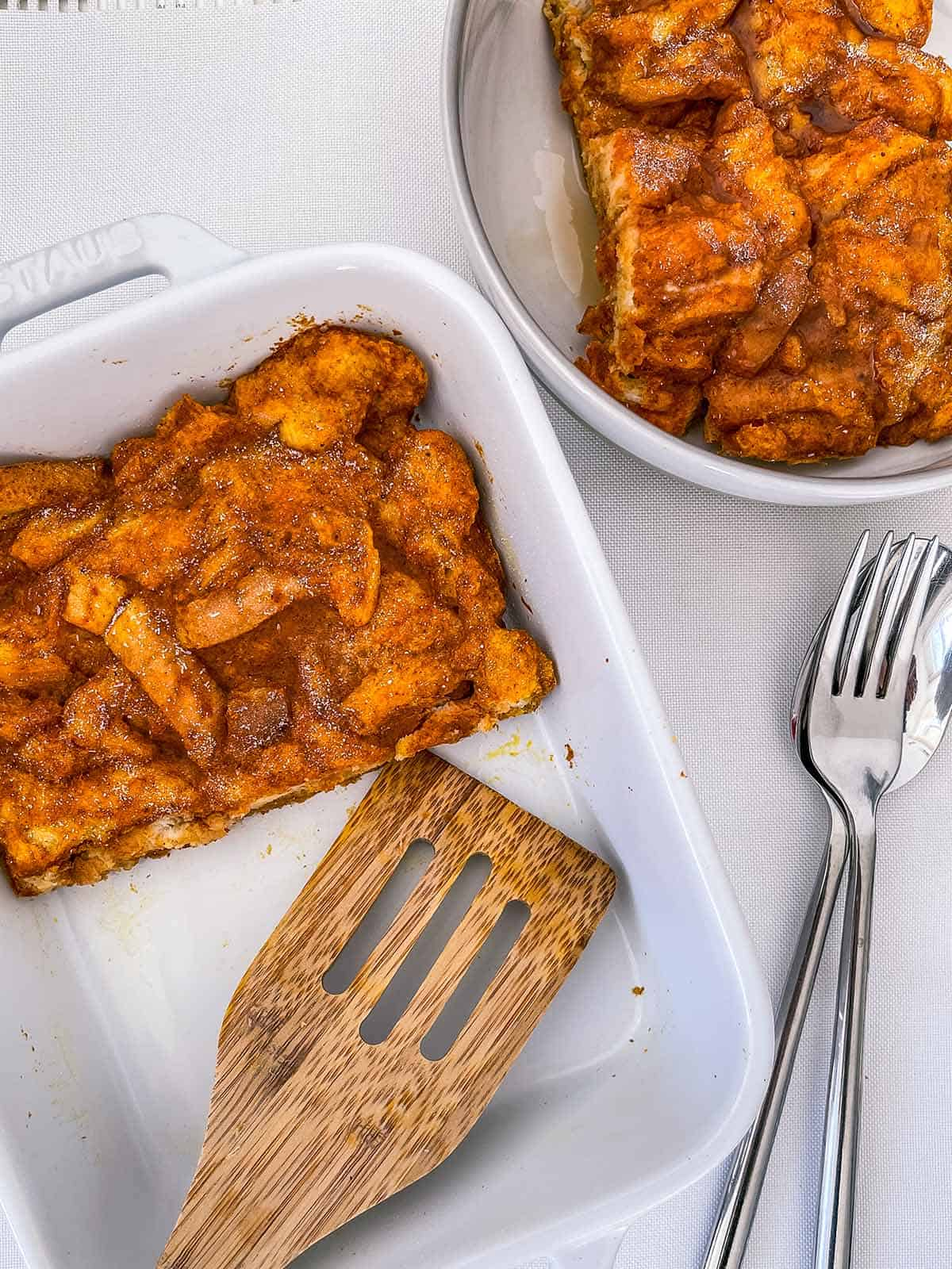 A dish of french toast casserole with a wooden spatula.